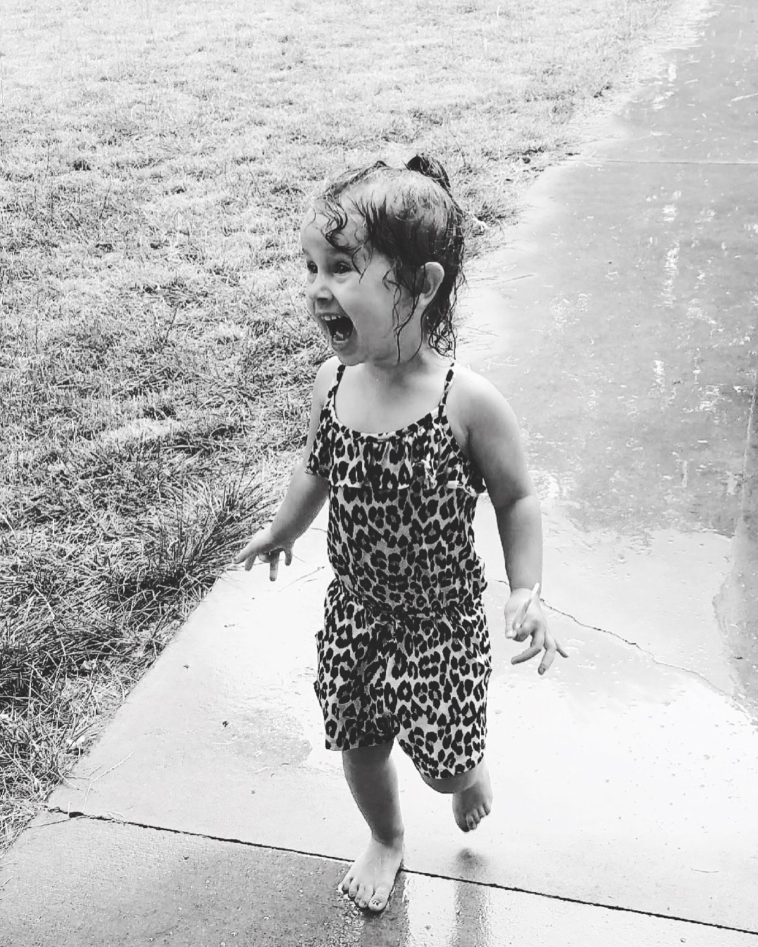 a little girl running and dancing in the rain on a driveway
