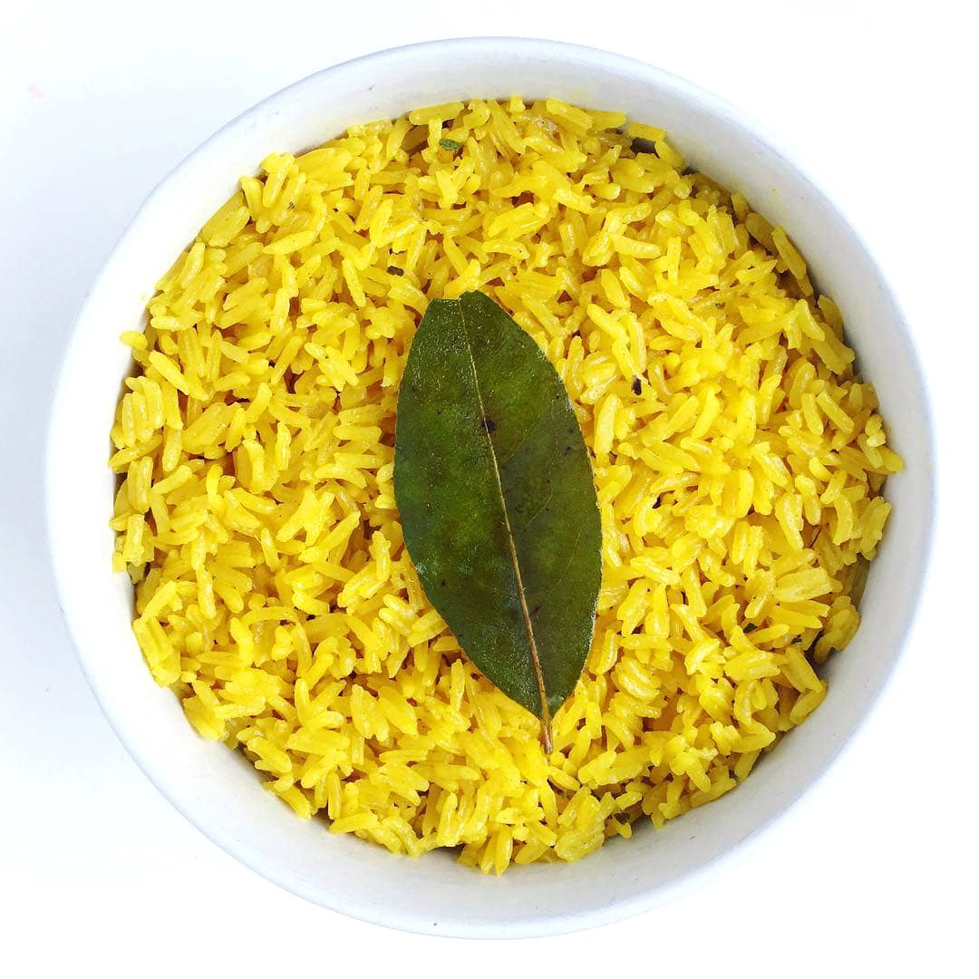 A brightly colored turmeric coconut rice in a small white ramekin topped with a single bay leaf