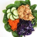 white bowl full of spinach, shredded carrots, purple cabbage, sliced cucumber, and slow cooker Asian honey chicken