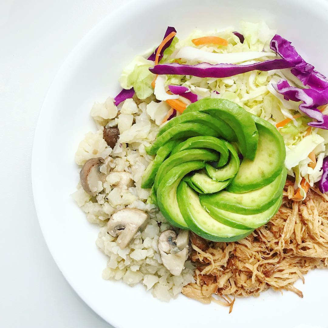white bowl with slow cooker Asian honey chicken, cauliflower rice, mushrooms, cabbage, and an avocado styled like a rose