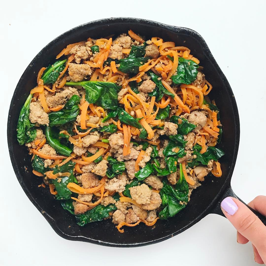 Sweet potato noodles, ground turkey, and wilted spinach in a cast iron skillet.