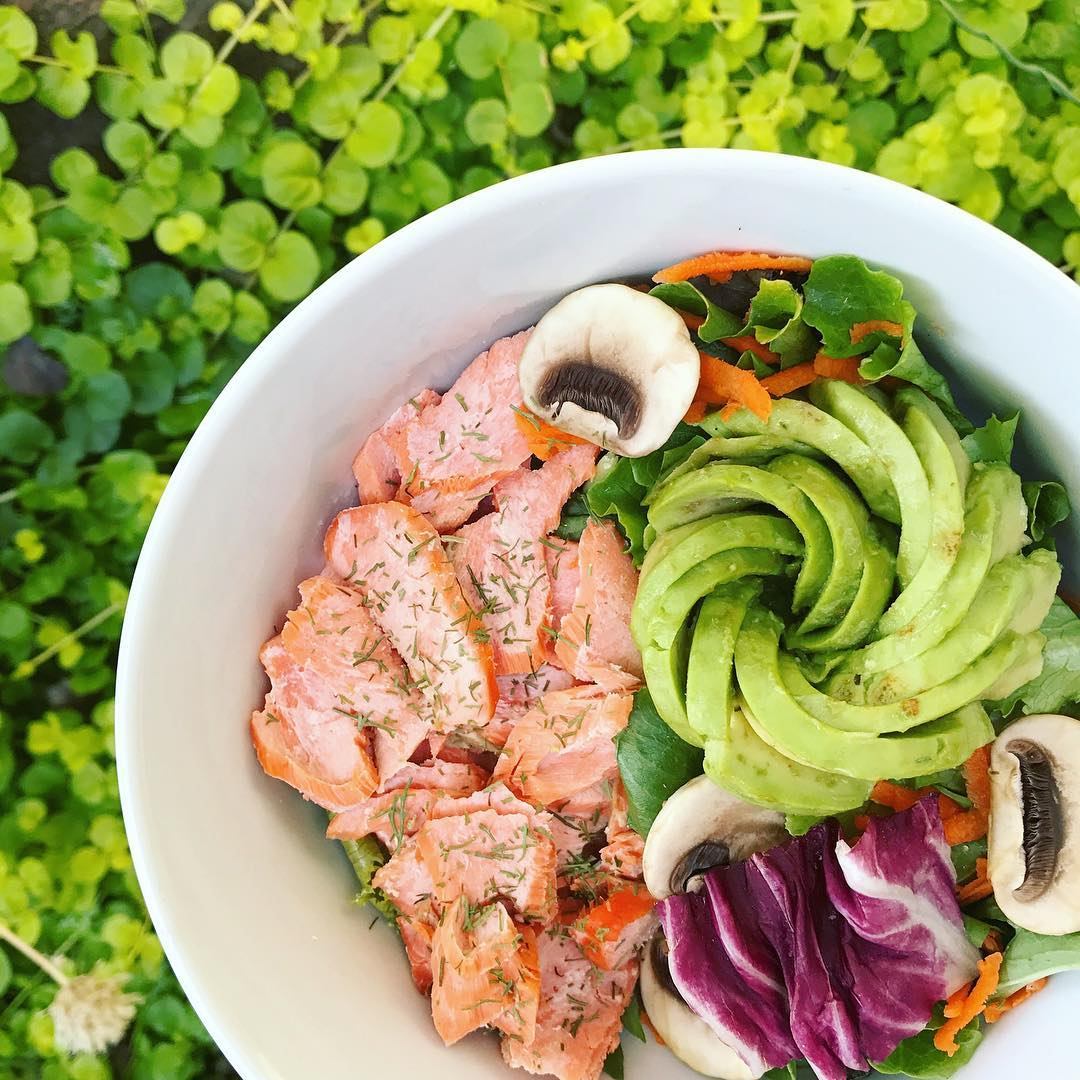 colorful food bowl full of spinach, salmon, mushrooms, and an avocado shaped into a rose with a vibrant green background
