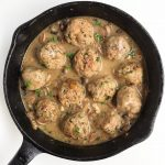 A cast iron skillet full of turkey meatballs and mushroom gravy
