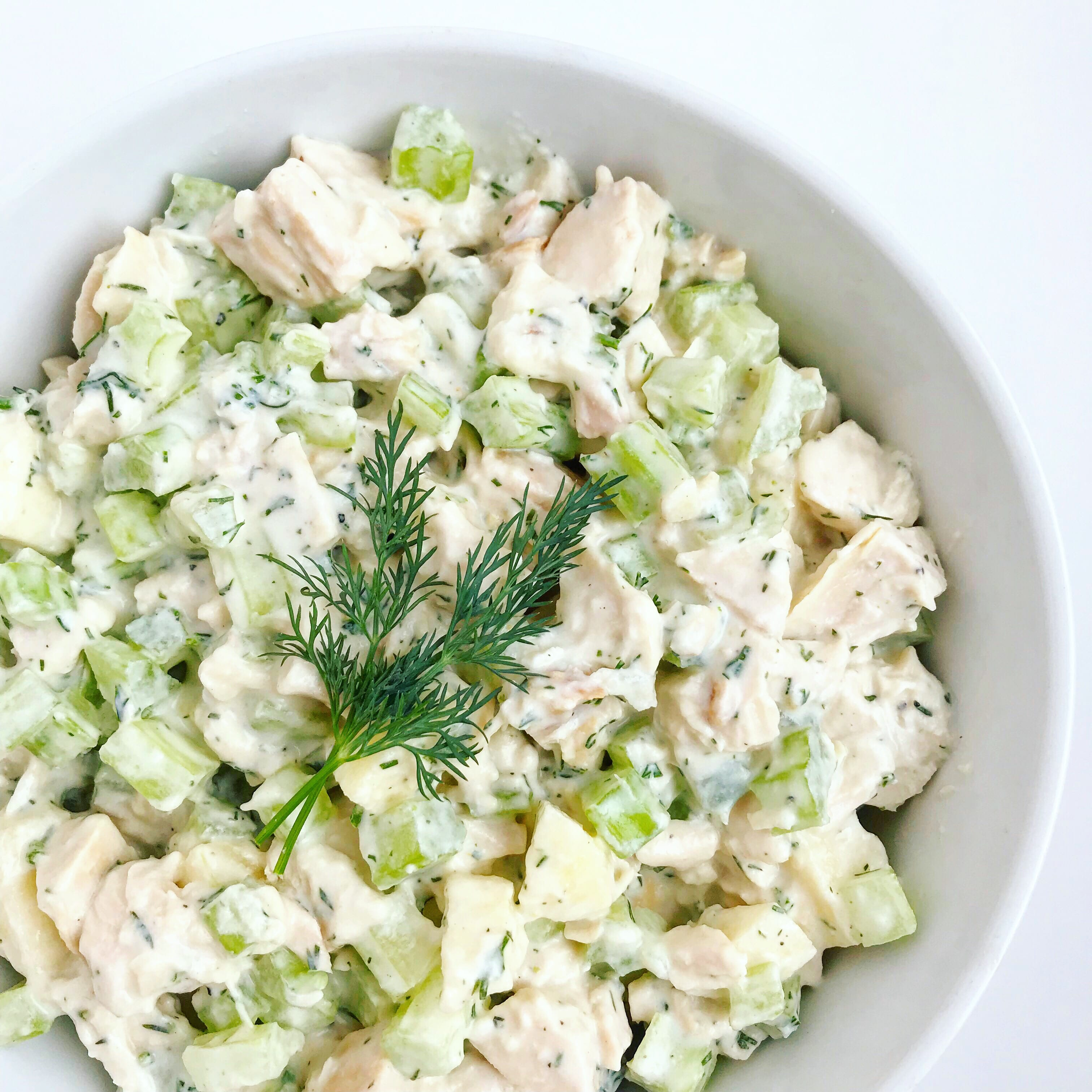 A bowl of dairy-free chicken salad, topped with fresh dill.