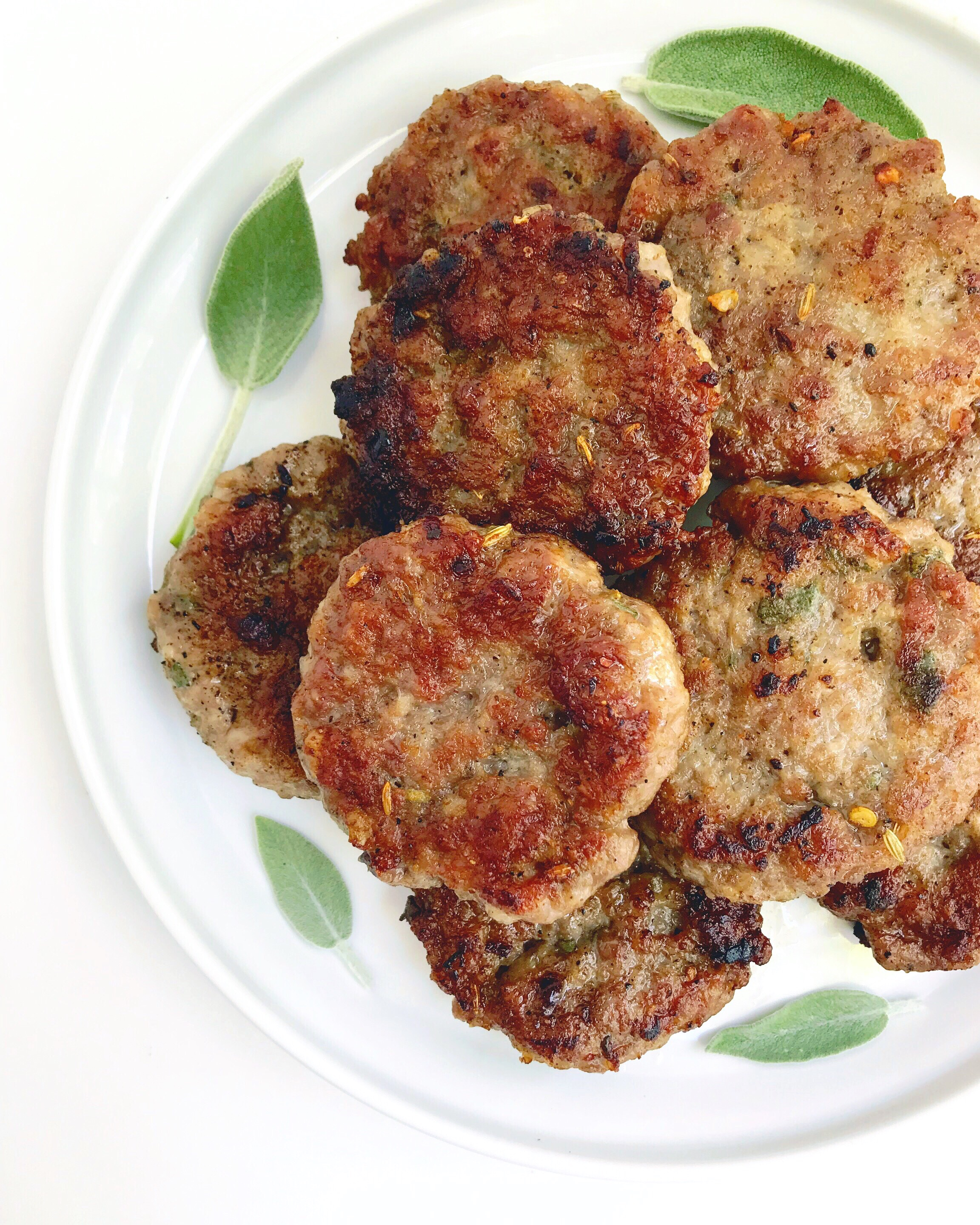 Plate of Maple Sage Breakfast Patties, garnished with fresh sage leaves.