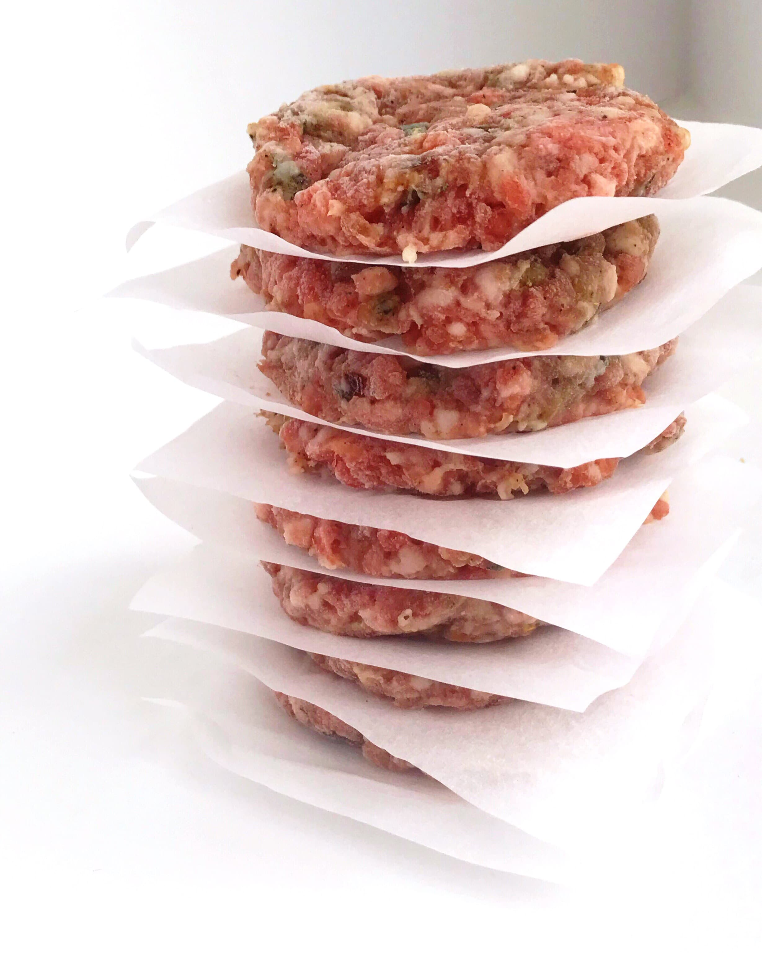 Stack of prepped Maple-Sage Breakfast Patties with parchment paper in between each patty.