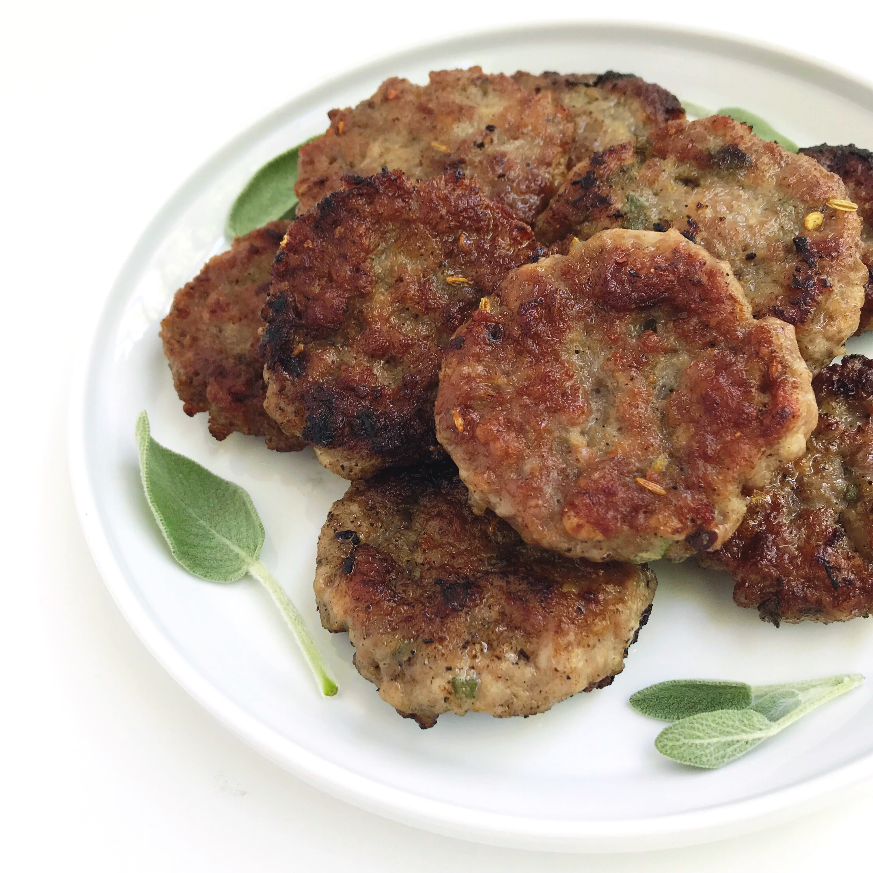 A plate of Maple-Sage Breakfast Patties, garnished with fresh sage leaves.