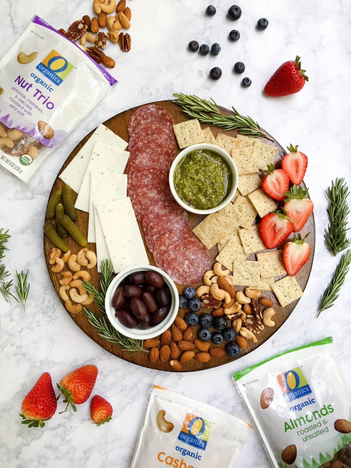 A charcuterie board that is gluten and dairy-free with a variety of ingredients such as meat, cheese, crackers, nuts, fruit, etc. Displaying O Organics Nuts in the background.