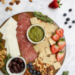 A gluten-free and dairy-free charcuterie board displaying meat, cheese, nuts, fruit, fresh herbs, crackers, olives, and pickles.