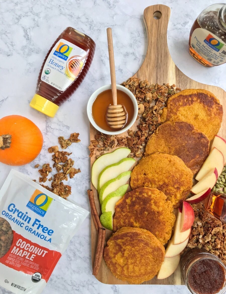 A wooden board with pancakes, apple and pear slices, maple syrup, honey, apple butter, granola, and pumpkin seeds. Also, featured is O Organics honey, maple syrup, and grain-free granola.