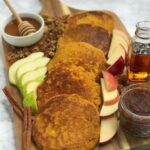 A wooden board with pancakes, apple and pear slices, maple syrup, honey, apple butter, granola, and pumpkin seeds