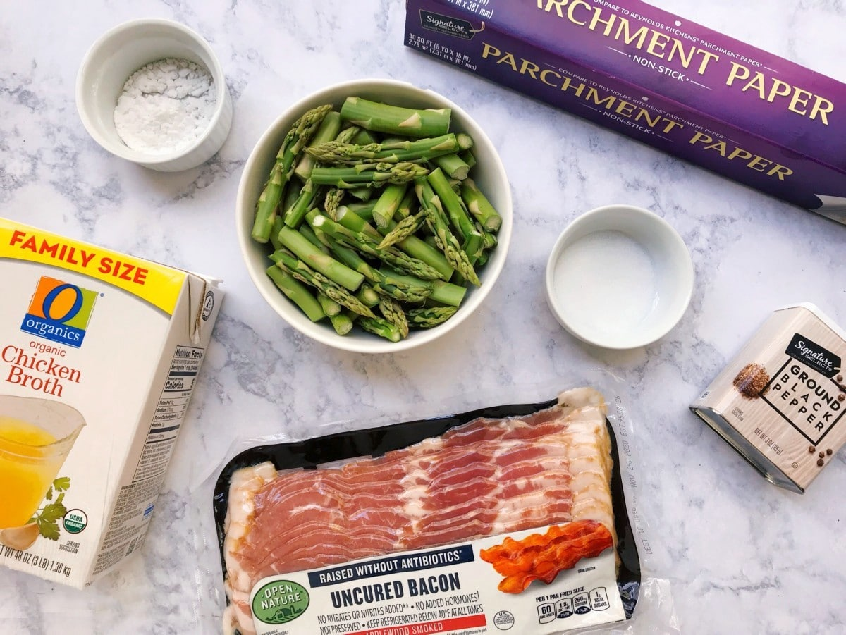 Product layout: bowl of asparagus, small bowl of salt, small bowl of potato starch, chicken broth, bacon, black pepper, and parchment paper