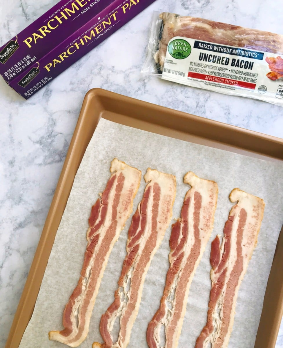 Four strips of bacon layed out on a baking sheet lined with parchment paper. Parchment paper and bacon in the background.
